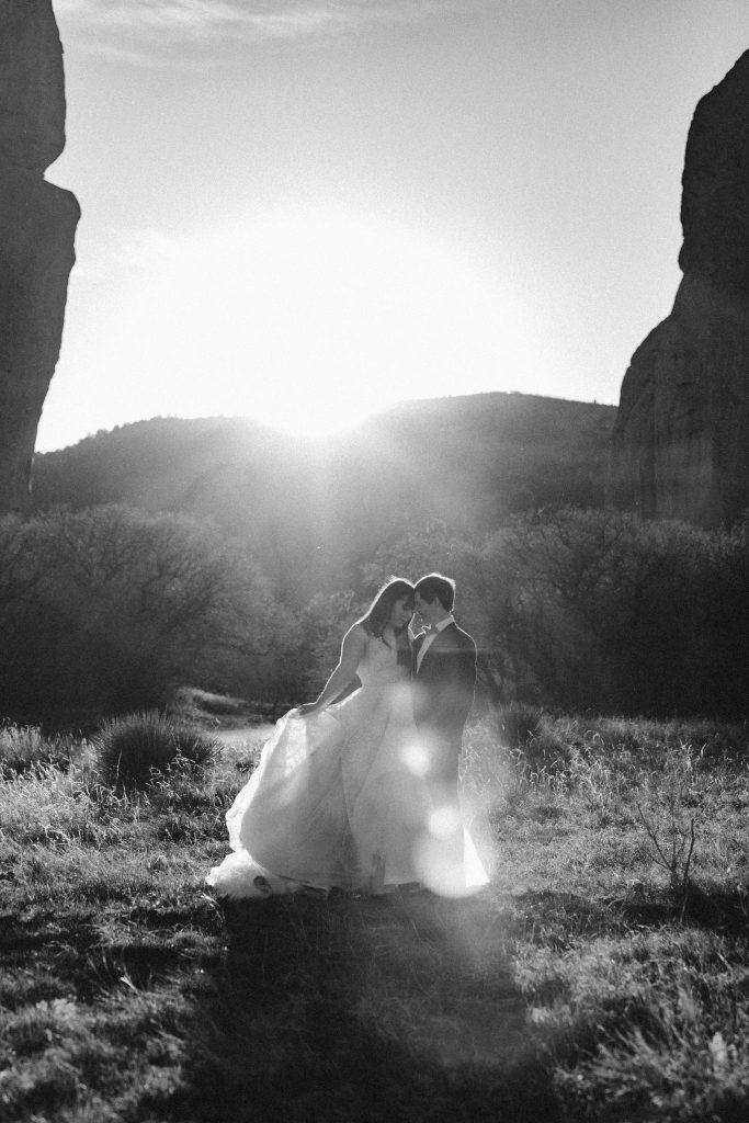 a black and white photo of a bride and groom wearing traditional wedding attire during their sunset garden of the gods elopement