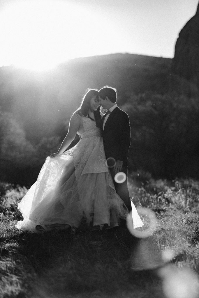 a black and white picture of a couple wearing traditional wedding attire posing in a grassy area at garden of the gods park during sunset with a giant lens flare