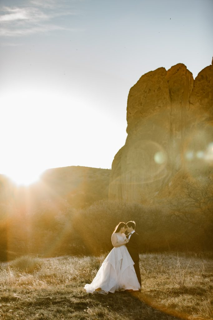 a female and male couple wearing wedding attire standing in a grassy area of the park during sunset at their garden of the gods elopement