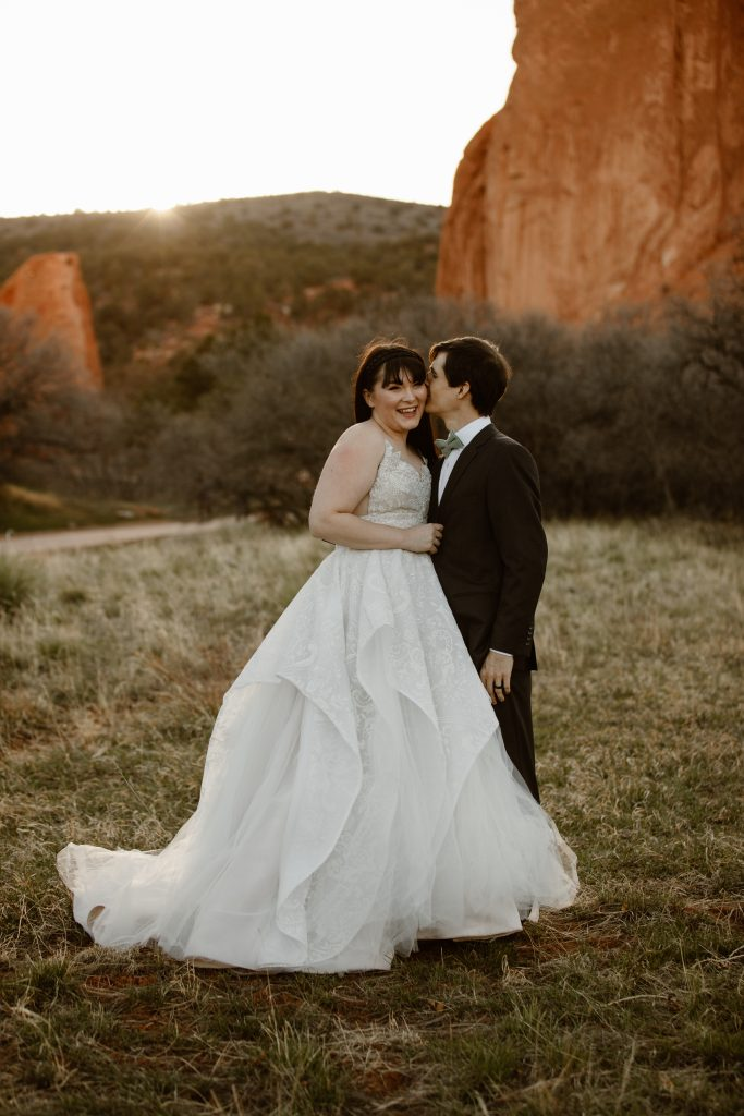 a white female wearing a beautiful white wedding gown is being hugged and kissed by her husband who is wearing a black suit while they're standing on the central garden trail at the garden of the gods park