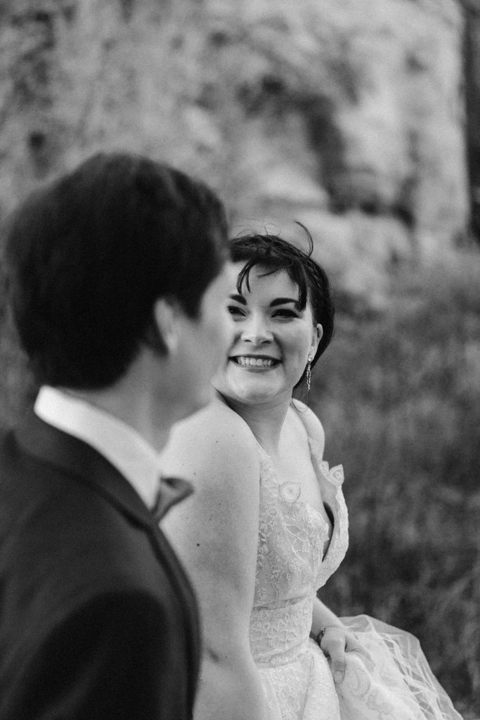a black and white photo of a close up of a bride while holding hands with her husband and walking and smiling at him