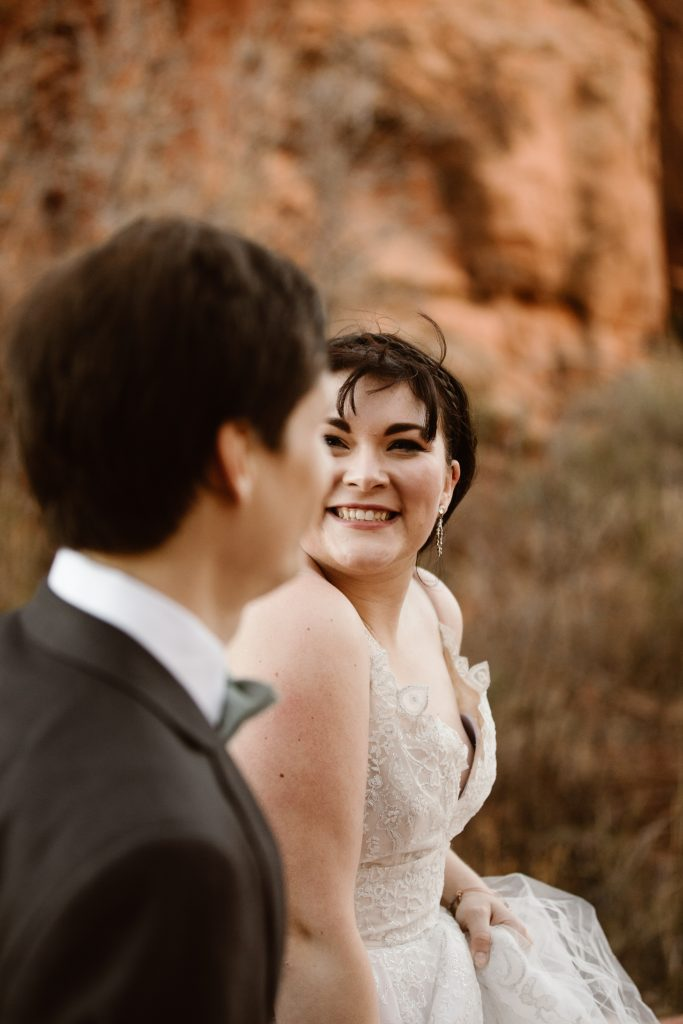 a close up of a bride wearing a white wedding gown and shes smiling while walking and looking at her husband