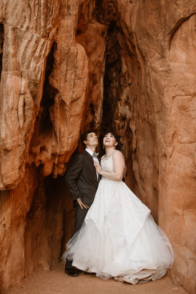 a bride and groom wearing traditional wedding attire are standing in a red rock formation cave while holding hands and looking up at the formation