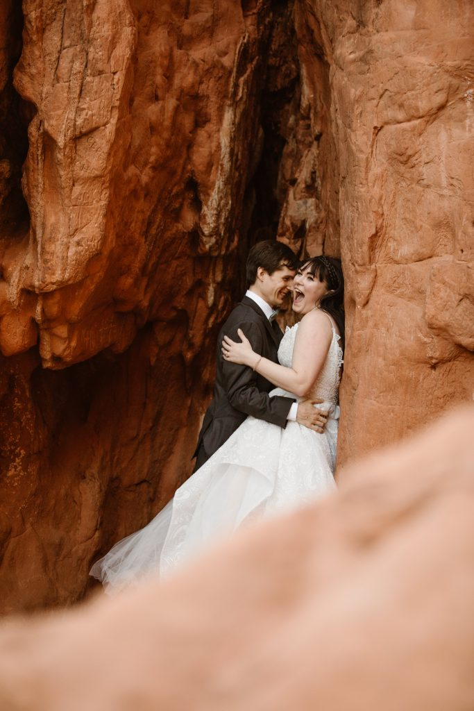 a bride and groom dressed in wedding attire pose against a red rock formation at the garden of the gods park