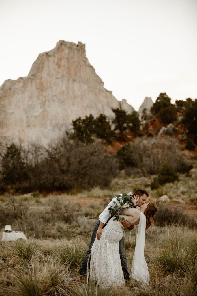 a couple wearing wedding attire are kissing in front of white rock at the garden of the gods park