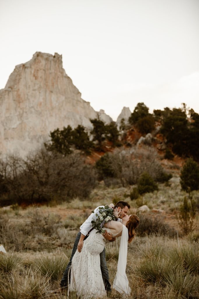 a male and female couple wearing traditional wedding attire is dancing in front of white rock at the garden of the gods park in colorado springs, colorado