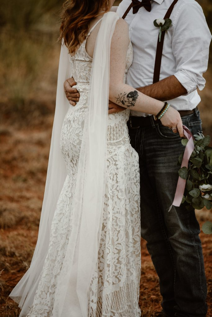 a close up of a couples wedding attire, the bride is wearing an ivory form fitting dress with tulle sleeves, and the male is wearing a white button up with jeans and brown suspenders