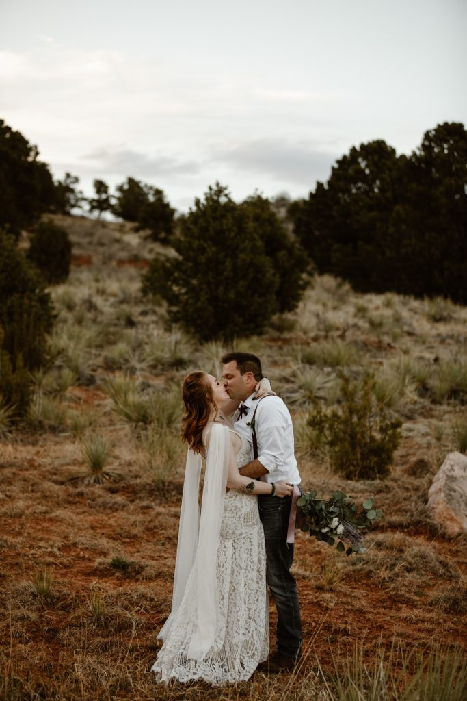 a couple is hugging and kissing while wearing wedding attire in a desert landscape at the garden of the gods park