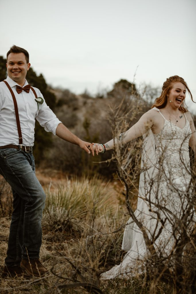 a bride and groom wearing wedding attire and walking hand in hand through a desert landscape at the garden of the gods park on their elopement day