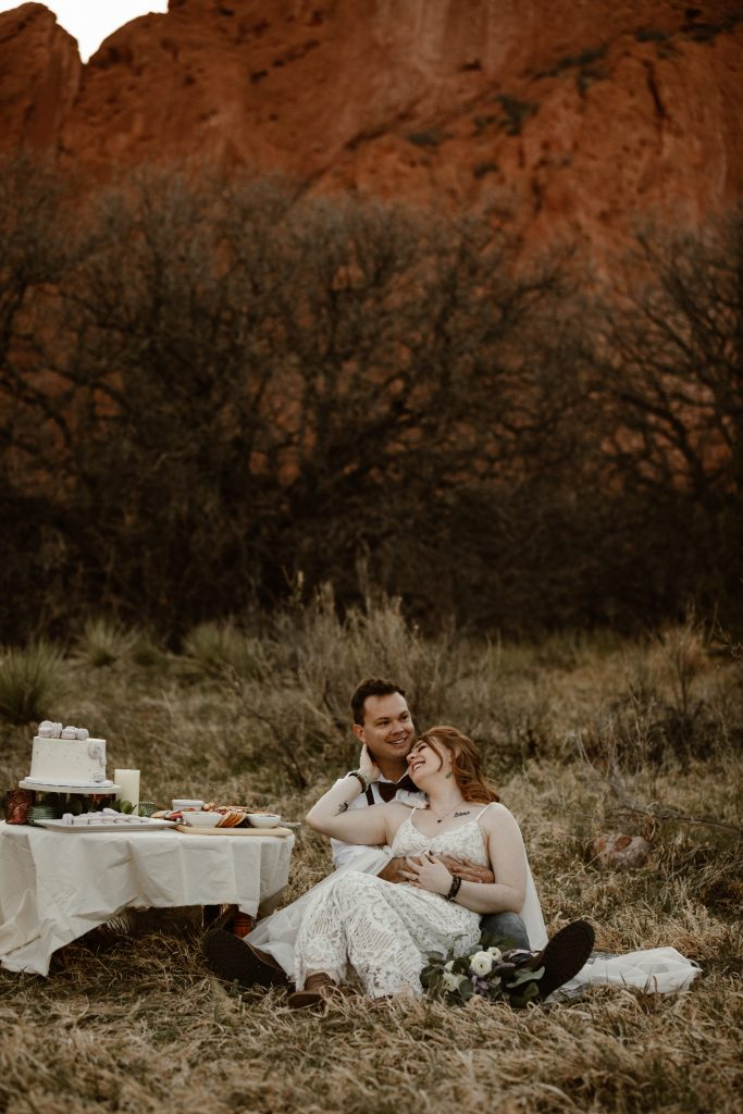 a male and female couple are sitting in a grassy area having a picnic at the garden of the gods park during their elopement