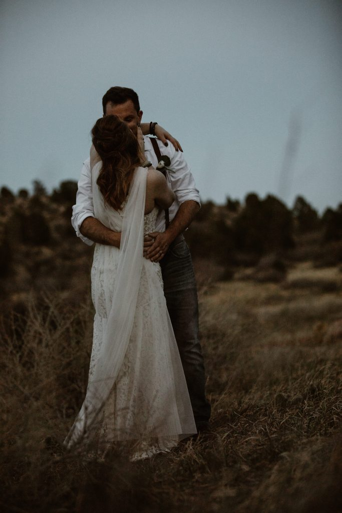 a bride and groom wearing wedding attire are slow dancing in a desert landscape during blue hour