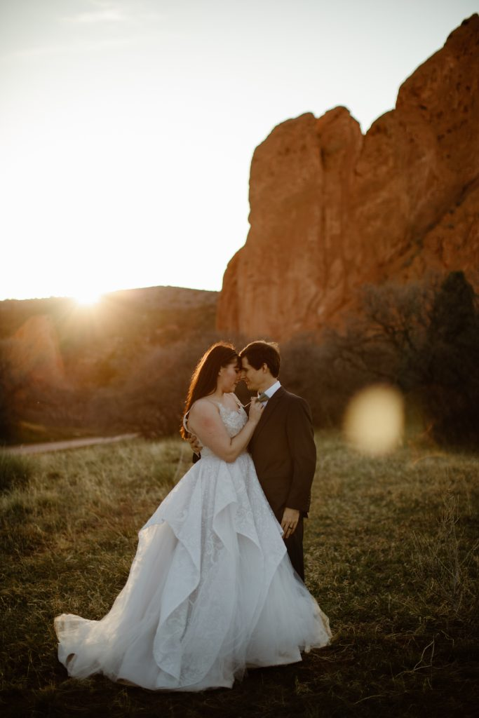 a bride wearing a white wedding gown and groom wearing a grey suit are posing in a grassy field at the garden of the gods park with red rock formations in the background