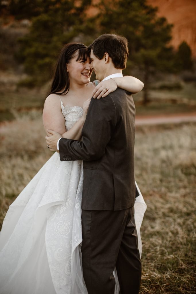 a bride wearing a white wedding dress and groom wearing a grey suit are slow dancing in a grassy area during their elopement at garden of the gods park