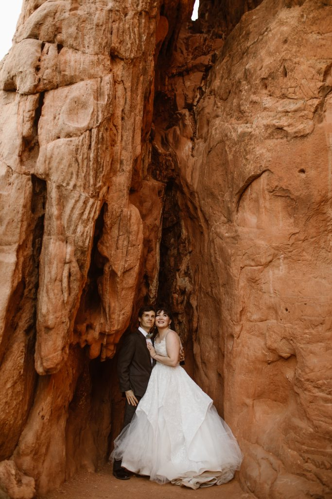 a bride and groom wearing black and white wedding attire standing in between two rock formations at the garden of the gods park during their elopement