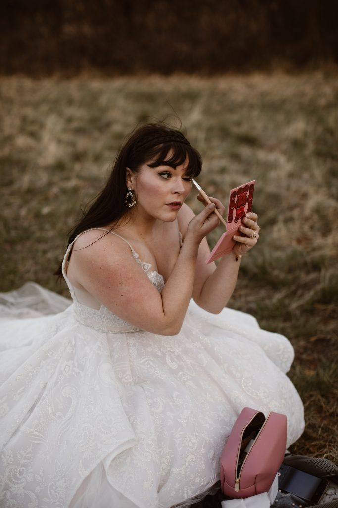 a bride is wearing a beautiful white wedding gown and doing her make up in a grassy area of the garden of the gods park getting ready for her elopement
