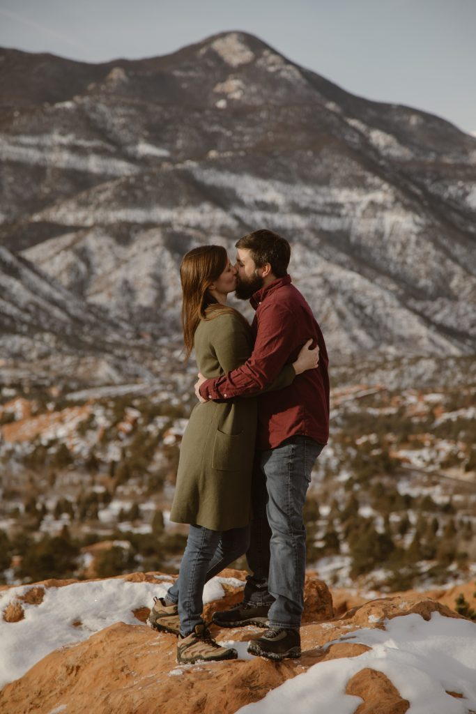 a couple standing on top of a rock on ridge trail at garden of the gods park with the mountains in the background