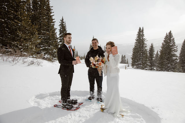 a couple wearing wedding attire standing in the snow in colorado during their elopement ceremony