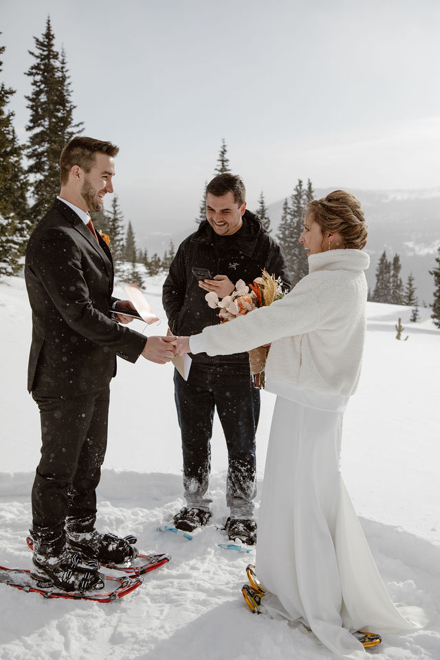 a male and female wearing wedding attire are standing in the snow having a wedding ceremony