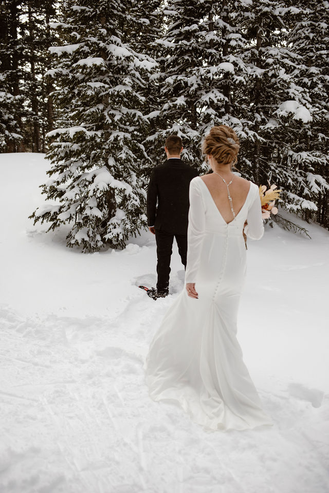 a man wearing a black suit is facing away from the camera as a women wearing a white wedding dress is walking up behind him in a snow covered forest