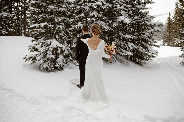 """a man and women dressed in wedding attire are having a """"first look"""" during their colorado winter wedding"""