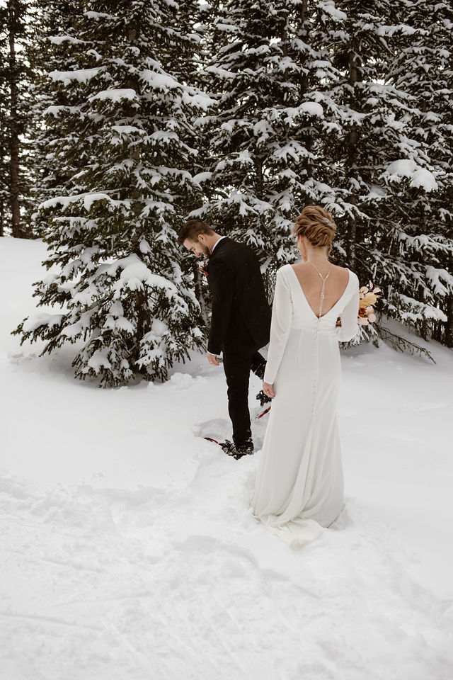 a man wearing a black suit is turning around while wearing snowshoes while a women wearing a white wedding dress is waiting for him to see her for the first time on their wedding day
