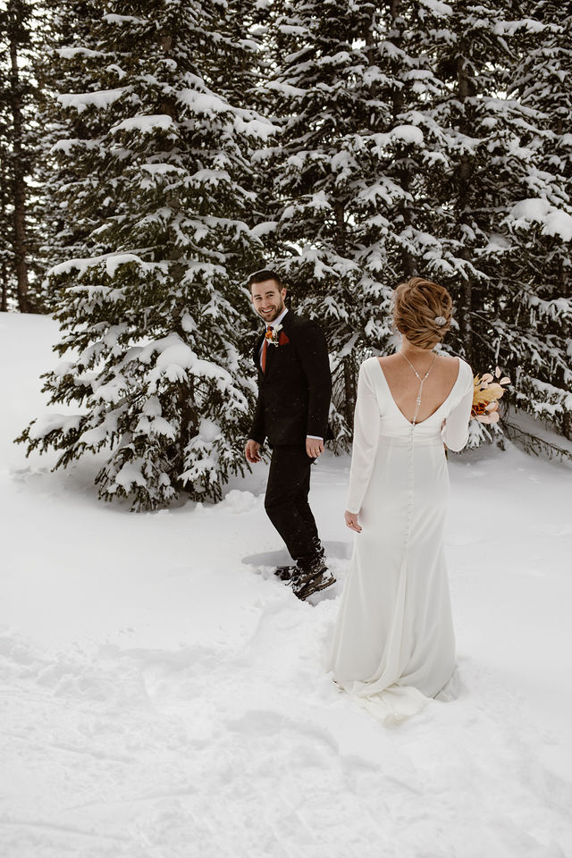 a male wearing a black suit is turning around in the snow while wearing show shoes to see his fiance for the first time on their elopement day
