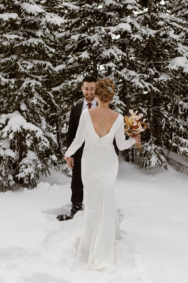 a man and women wearing wedding attire and snowshoes have a first look in the snow covered colorado forest