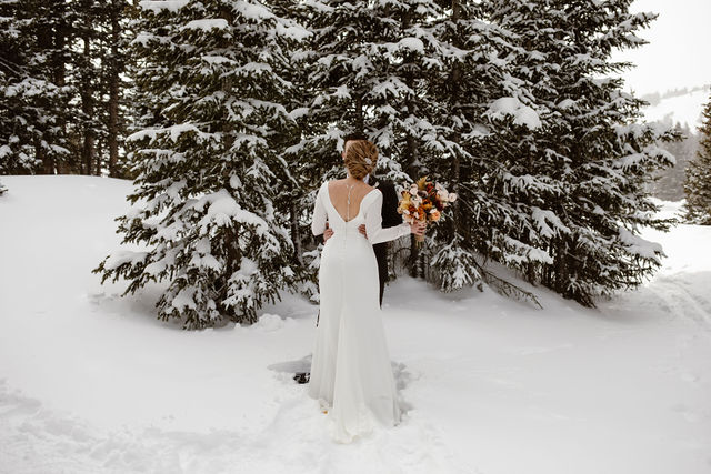a man and women wearing wedding attire are hugging in a snow covered forest in colorado