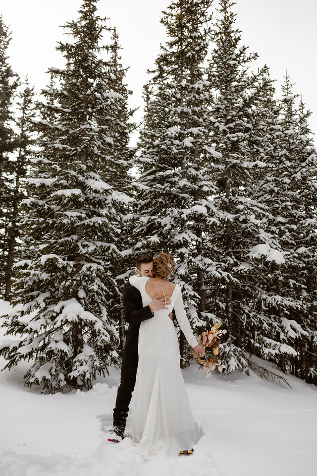 a male and female are hugging in a snow covered colorado forest