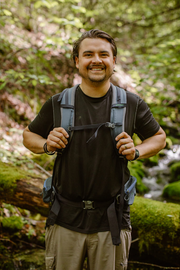 a portrait of alex white wearing a black shirt and blue backpack in a moss covered lush green forest