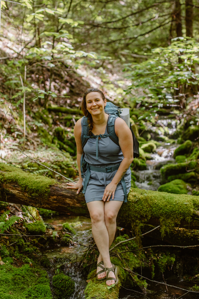 a portrait of kelly shoul wearing a blue dress and blue hiking backpack sitting on a moss covered log in a green lush forest with a river in the background