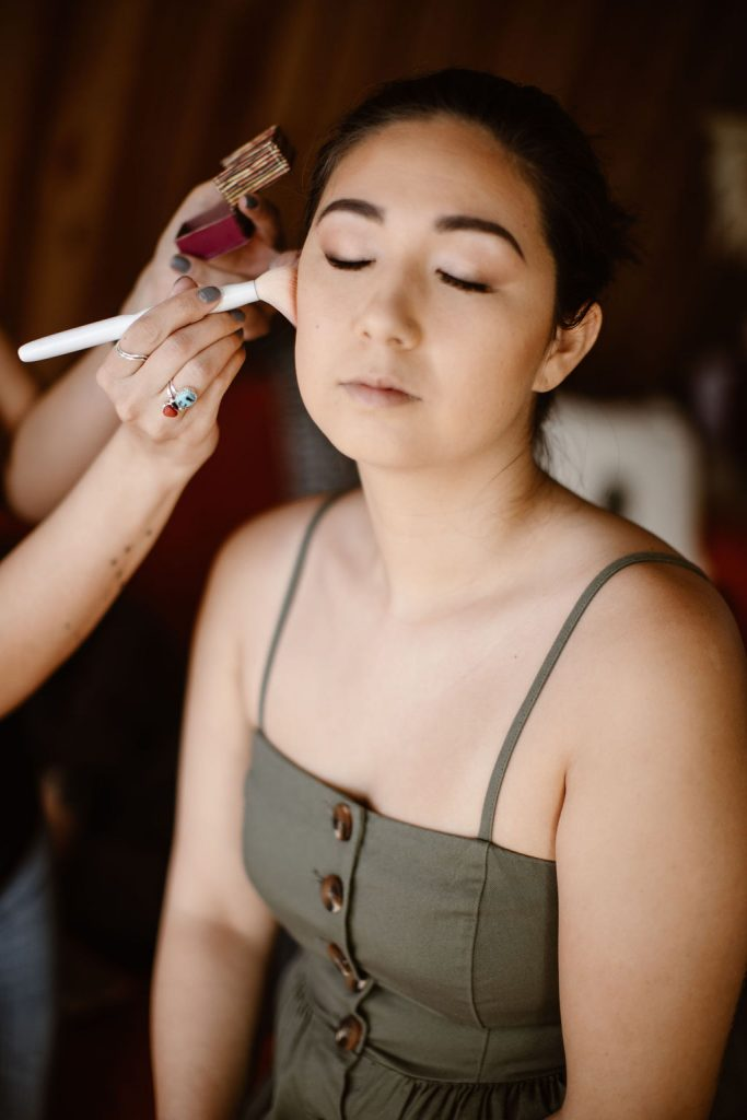 a bride getting her make up done professionally on the morning of her elopement day