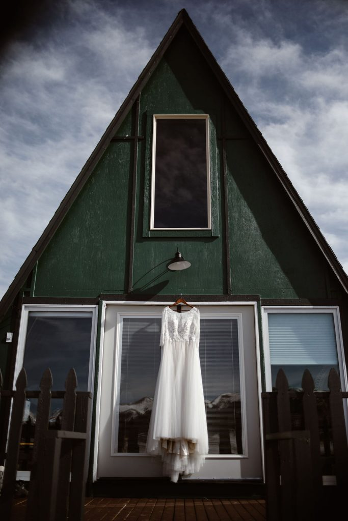 a white wedding dress hanging on a door on a green A frame cabin in the mountains