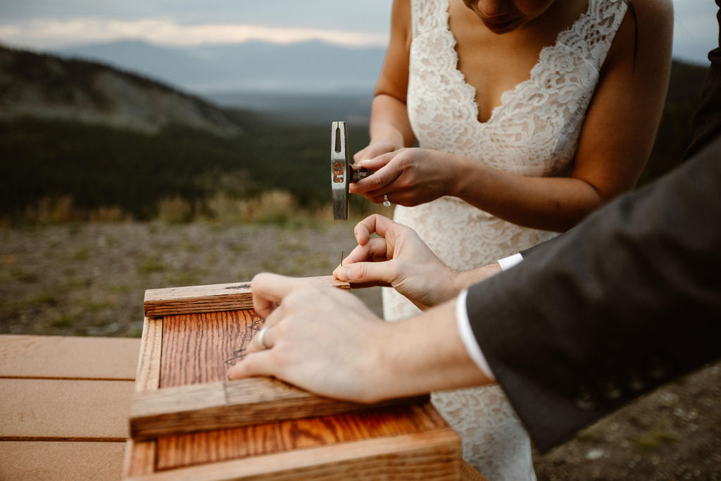 a bride and groom nailing shut a time capsule on their elopement day