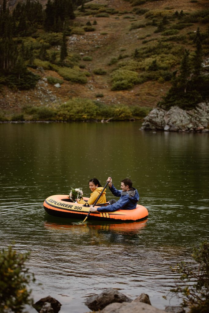 a couple in an orange raft wearing yellow and blue rain jackets are paddling around an alpine lake in colordao