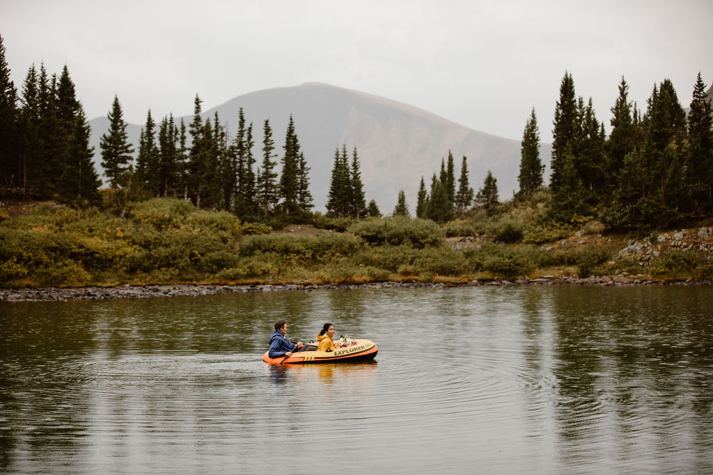 a couple wearing rain jackets are paddling in an orange inflatable pack raft in an alpine lake in colordao