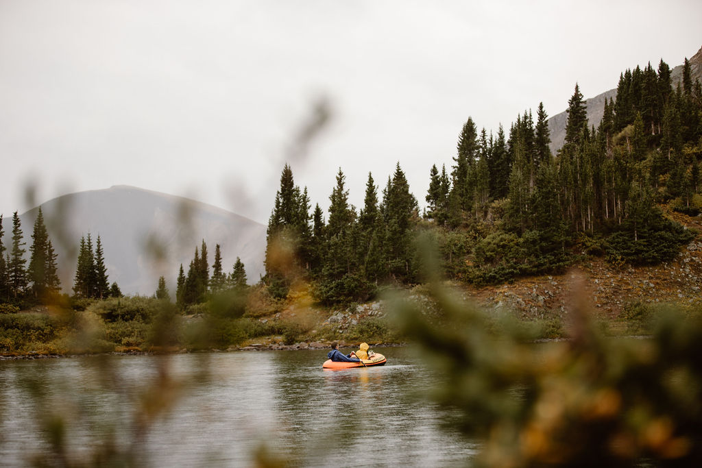 a couple in an orange raft paddling in an alpine lake in colorado on their elopement day