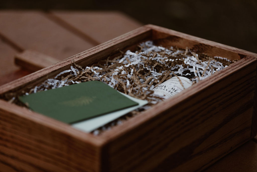 a wooden box with two vow booklets and a bottle of wine in it