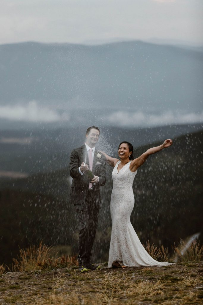 a male and female bride and groom popping a bottle of champagne at the top of a mountain pass in colorado