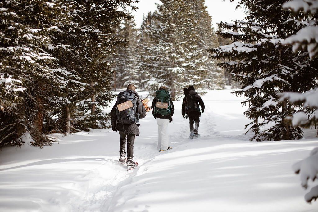 three people snowshoeing through deep snow in a forest