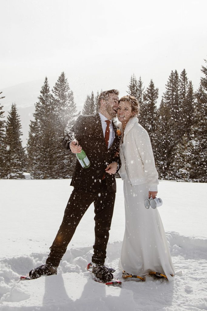 a bride and groom wearing snowshoes is popping a bottle of champagne to celebrate their elopement