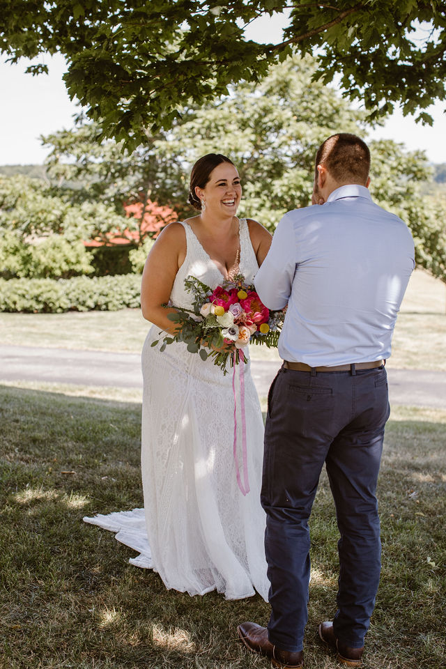 a bride and groom standing in the grass in the shade sharing a first look moment