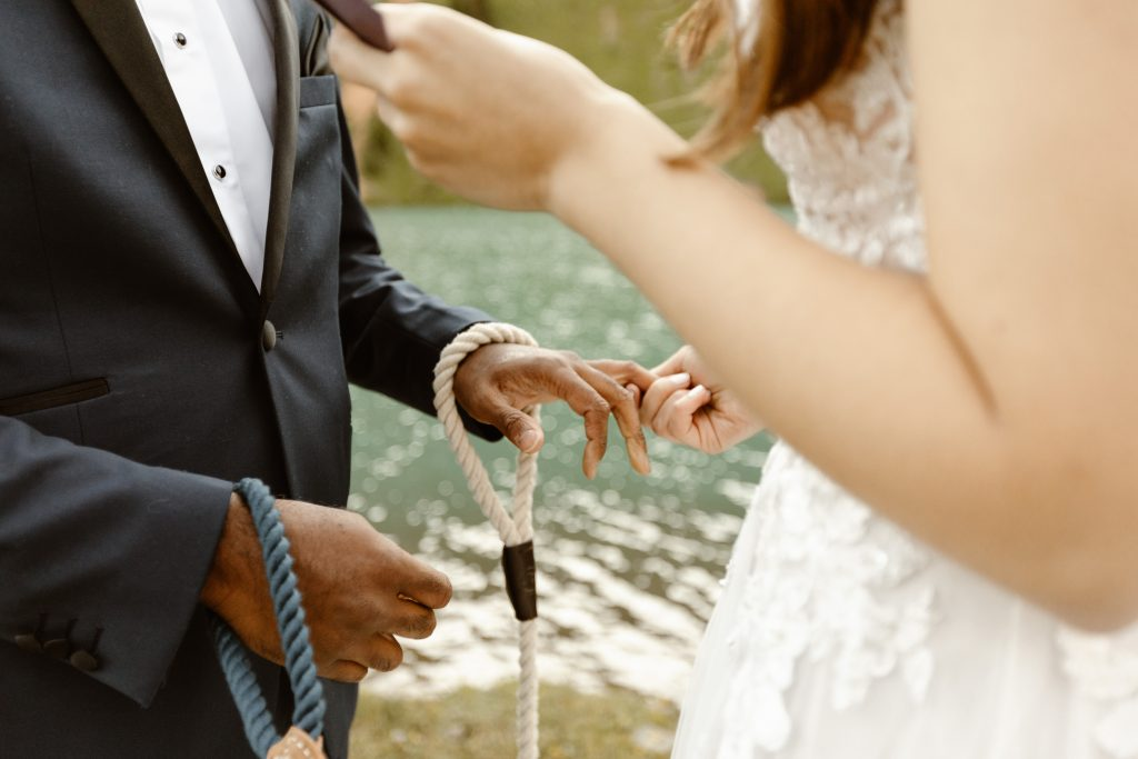 A CLOSE UP OF A COUPLE HOLDING HANDS DURING THEIR ELOPEMENT CEREMONY