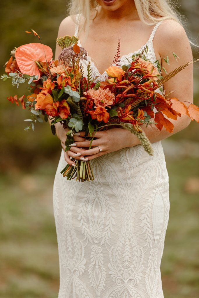 a white female in a white lace wedding dress holding a beautiful orange floral bouquet