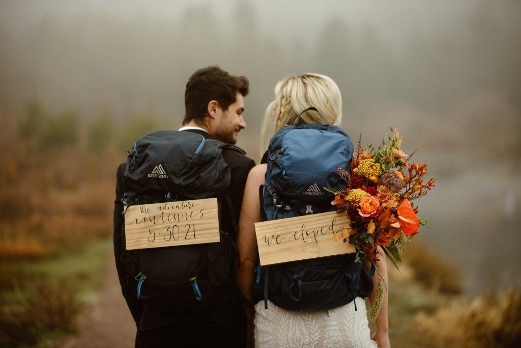 """a couple wearing backpacks with signs that read """"we eloped"""" hanging off of them"""