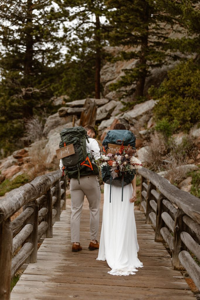 a couple walking across a bride while holding hands wearing decorated backpacks during their adventure elopement