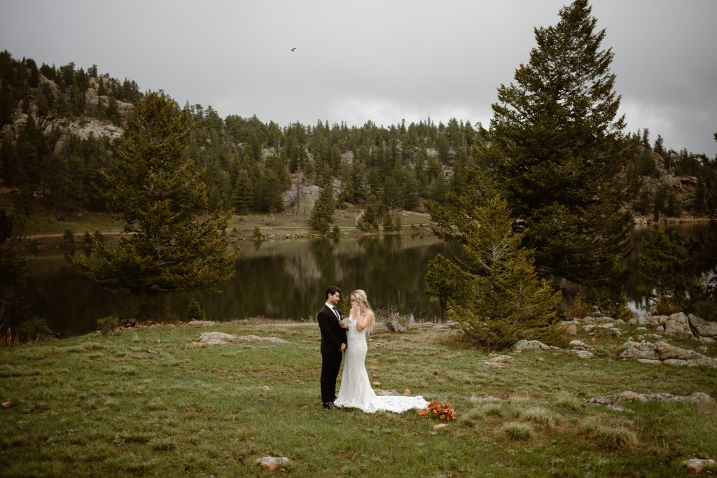 a couple standing in a lush green grassy area during their elopement ceremony