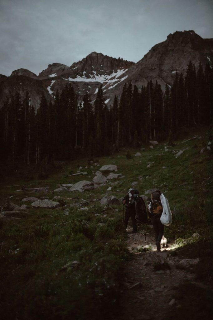a couple hiking in the dark towards a snow covered mountain with head lamps on