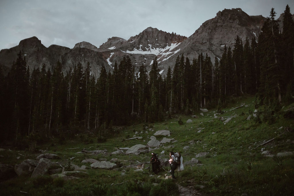 a couple hiking up to a snow covered mountain in the dark in the morning of their elopement