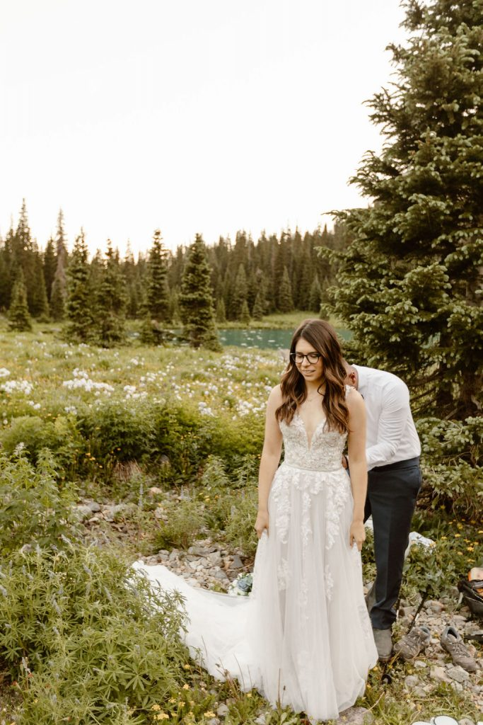 a bride and groom wearing wedding attire are getting dressed in the middle of the Colorado wilderness on the morning of their elopement day